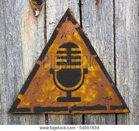 Microphone Icon on Rusty Warning Sign.