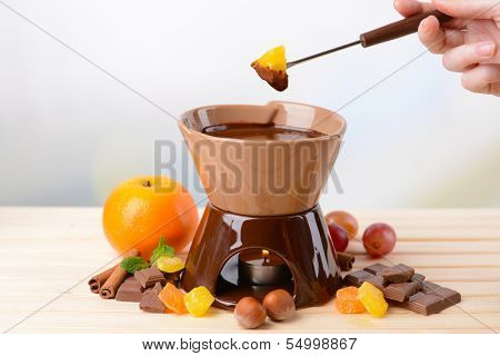 Chocolate fondue with fruits, on wooden table, on light background
