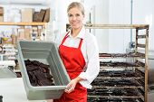 Portrait of happy female worker showing beef jerky in basket at butcher's shop