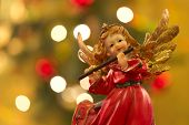 foto of figurine  - Angel figurine with flute over bokeh background on christmas