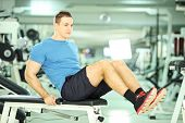 image of abdominal muscle man  - Young man seated on a bench exercising abdominal muscles in a fitness club - JPG