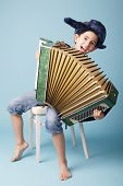stock photo of accordion  - little funny accordion player on blue background - JPG