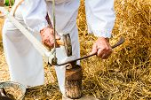 foto of scythe  - Man is sharpening a scythe which is used to mow grain - JPG