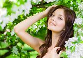 picture of nearly nude  - Portrait of young woman touches her face standing near the blossomed tree in the park - JPG