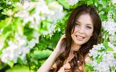 stock photo of nearly nude  - Portrait of pretty woman touches her face standing near the flowered tree in the park - JPG