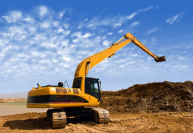 pic of power-shovel  - Orange excavator at Construction irrigation canal in Desert - JPG