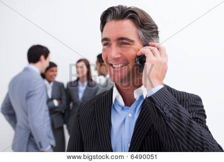 Attractive Manager On Phone With His Team In The Background