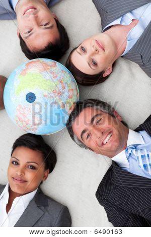 Multi-ethnic Business Team Lying On The Floor Around A Terrestrial Globe