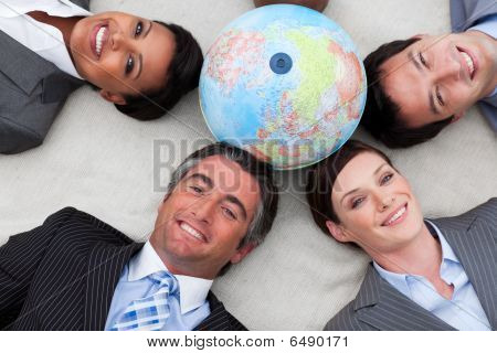 Business People Lying On The Floor Around A Terrestrial Globe
