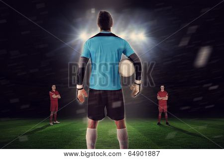 Composite image of goalie facing opposition against football pitch under spotlights