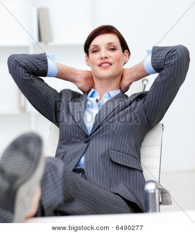 Businesswoman Leaning Back On A Chair With His Feet On The Desk