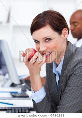 Businesswoman Eating A Fruit At Work