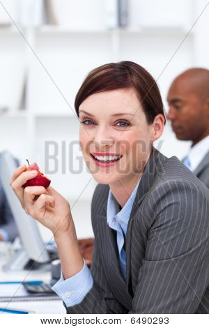 Portrait Of A Smiling Businesswoman Eating An Apple