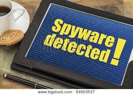 spyware  detected alert on a digital tablet with a cup of coffee