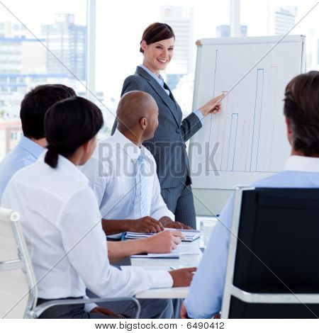 Smiling Manager Reporting Sales Figures To Her Team