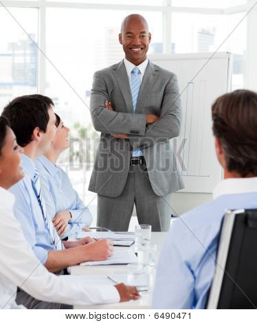 Confident Manager Reporting Sales Figures To His Team