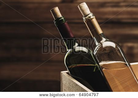 Bottle of red and white wine in wooden box