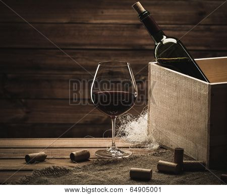 Bottle and glass of red wine on a wooden table