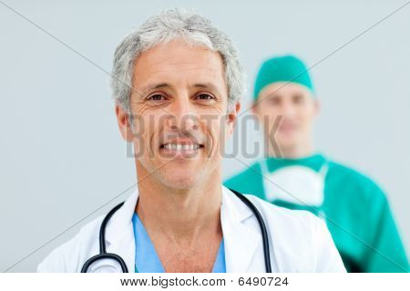 Close Up Of A Senior Doctor Standing In Front Of His Team