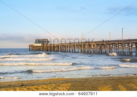 Sunrise over Balboa Pier shows the beautiful orange light, blue sky and wave pattern framed against the wooden structure of the pier.
