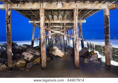 An image of the Balboa Pier in Orange County California early in the morning shows the structural detail and surrounding beauty of the ocean.  Shot using a technique called light painting.