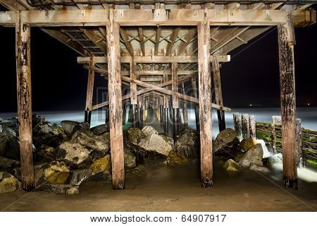 A light painted image of Balboa Pier underside taken at 4:00 AM with a slow exposure shows the intricate detail of the structure.  The ocean is lit from lights on top of the pier.