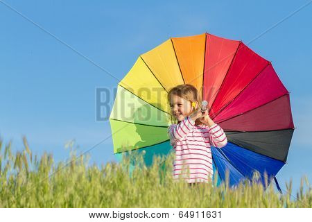 Girl stands in meadow with green grass against blue sky, watching sun and holding colored umbrella