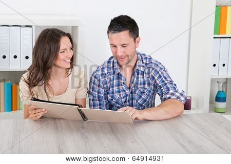 Happy Couple Looking At Photo Album
