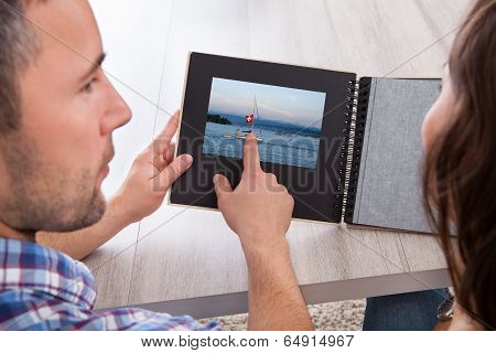 Young Man Pointing On Photo Album