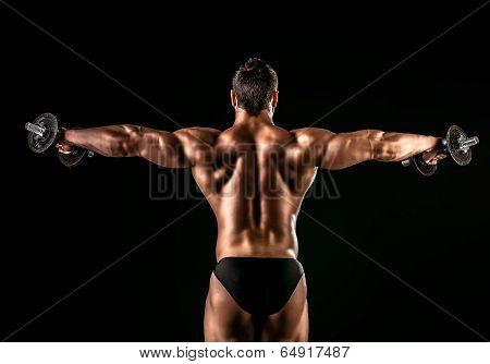 Beautiful muscular man bodybuilder posing back over dark background.