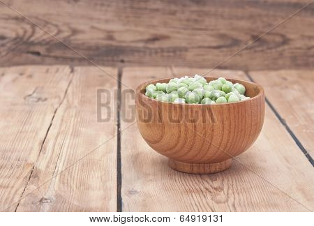 Frozen peas in a wooden  bowl on a wooden table