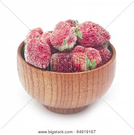 Frozen strawberries in a wooden bowl on white background