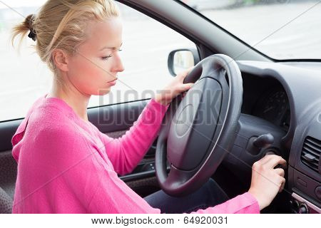 Female car driver starting the engine.
