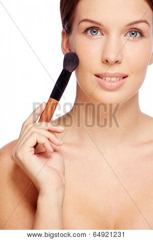 Fresh girl applying rouge with brush over white background