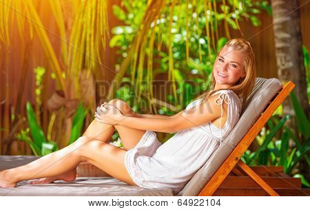Cute female on tropical resort, sitting on deckchair and taking sun bath, enjoying exotic nature, summer vacation on Maldives