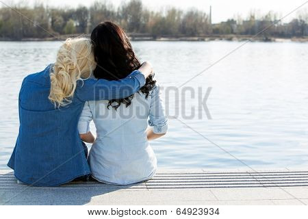 Friendship. Best friends sitting by the river