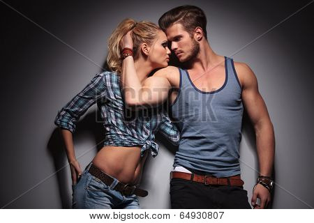 casual sexy man embracing his woman and reveals his biceps, studio shot