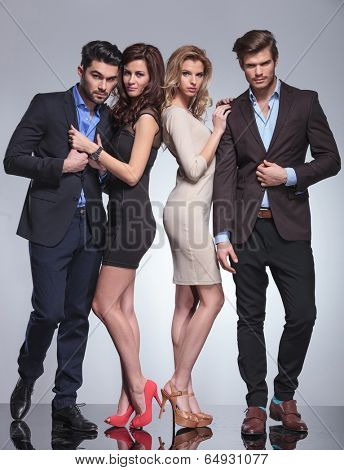 young women and their boyfriends posing in studio in elegant clothes