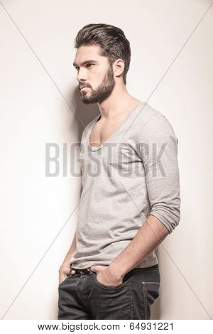 side view of a sexy young man with hands in his pockets in studio