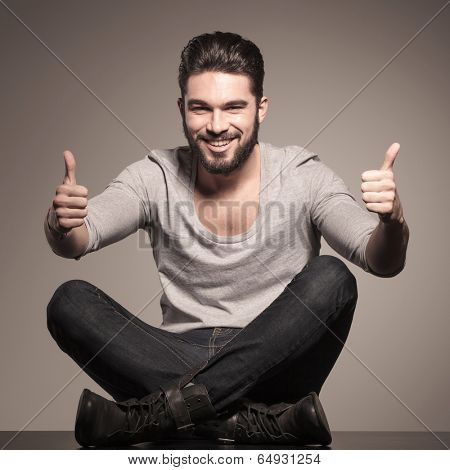 happy young casual man sits and make the ok thumbs up hand sign