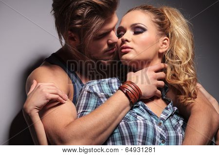 sexy muscular man embracing his girlfriend in studio