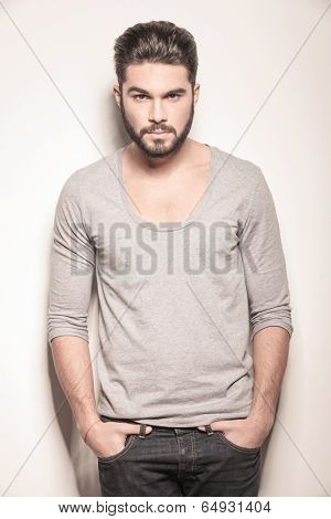 young muscular man looking away while standing close to his girlfriend, studio shot on gray background
