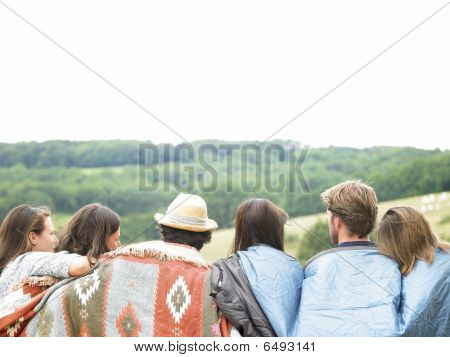 Rear View Of Friends Outdoors With Blankets