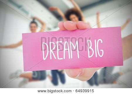 Woman holding pink card saying dream big against fitness class in gym