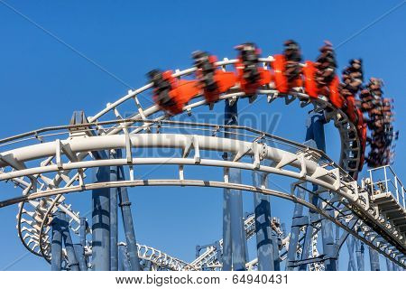 Roller coaster ride under blue sky.