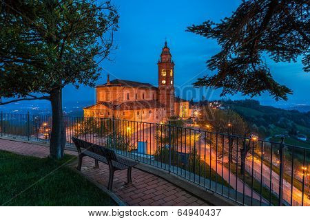Bench on walkway and view of illuminated church on background in the morning in Piedmont, Northern Italy.