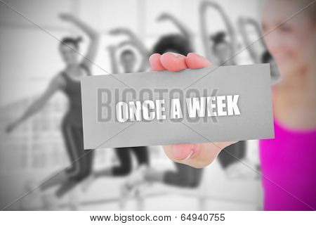 Fit blonde holding card saying once a week against fitness class in gym