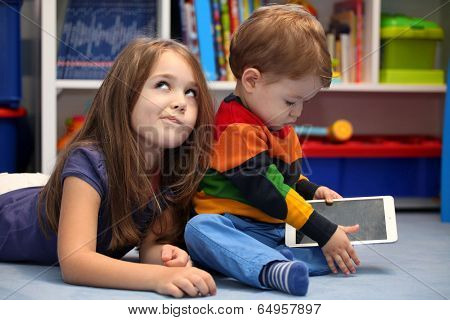Disappointing Girl With Her Little Brother Using A Tablet Computer