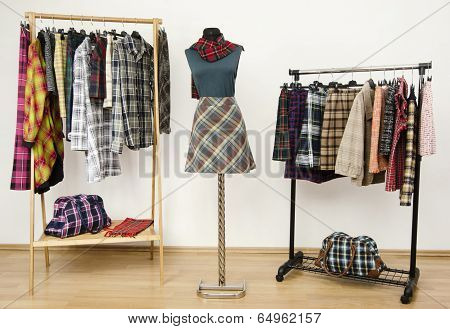 Wardrobe with tartan clothes arranged on hangers and an outfit on a mannequin.