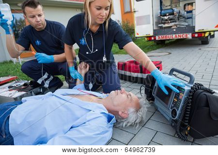 Paramedics checking pulse of unconscious senior man lying on street